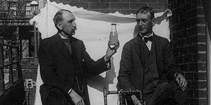Two men standing outdoors with small still, one of them holding up bottle of liquor